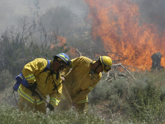 Hurricane Fire Department Firefighters works on digging a fire break as flames from the Snow Fields Fire continue to consume brush behind them Friday, May 13, 2006 near Exit 33 on Interstate 15.