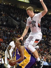 Los Angeles Lakers guard Jordan Clarkson (6) gets Portland Trail Blazers center Mason Plumlee (24) up in the air with a head fake during the first half of an NBA basketball game in Portland, Ore., Saturday, Jan. 23, 2016.