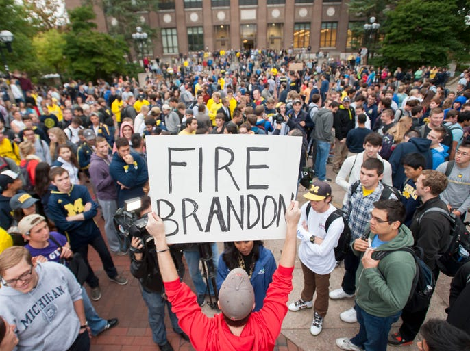 Law student Edward Mears holds a sign during a protest on the Diag, Sept. 30, 2014, on the campus of the University of Michigan over the recent football game against Minnesota when quarterback Shane Morris was left in the game after receiving a concussion. The protesters called for the firing of Athletic Director Dave Brandon.