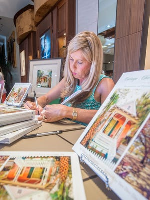"""Author Sharon Duplantis signs copies of her new book """"Cottage Charm in Historic Seville, Treasures of the Pensacola Historic District"""" during a reception at Jewelers Trade Shop in downtown Pensacola on Thursday, June 14, 2018."""