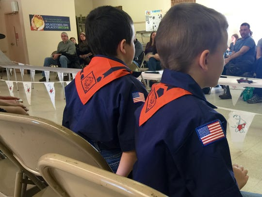 Zachary Walker and Jacob Beaver watch the Pinewood Derby competition.