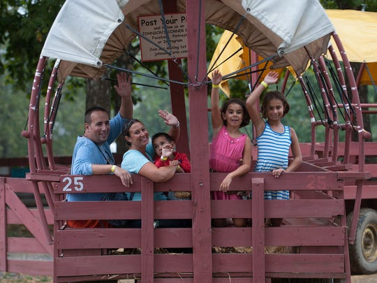 Members of the AmAlfitano family (from left) Paul, Kira Vaughn, Eve and Gwen wave from the Hay Ride at the at the Johnson Farms in Medford during the Fall Harvest Festival.