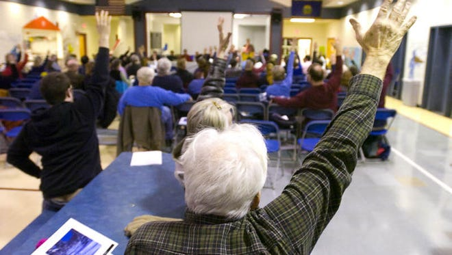 Residents vote during the Bolton Town Meeting in 2011.