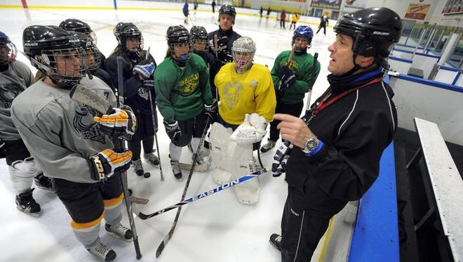 Leo Fusilli, right, talks with players on the Webster Youth Hockey Lady Cyclones under 14 travel team during a practice at Webster Ice Arena.