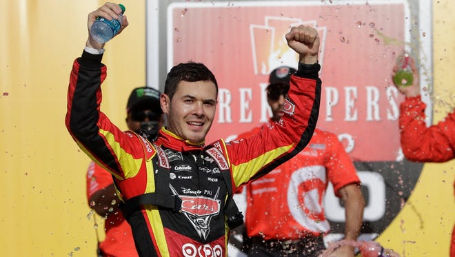 Kyle Larson raises his arms after exiting his car after winning a NASCAR Sprint Cup series auto race, Sunday, June 18, 2017, in Brooklyn, Mich.