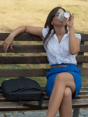 woman with coffee in a park
