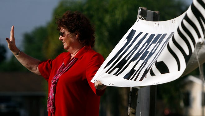 Destiny Diaper Bank founder Rebecca Hines waves to passersby along Lee Boulevard in Lehigh Acres Friday.