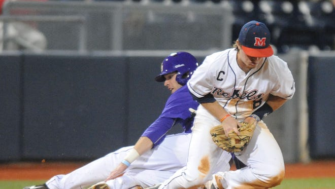 LSU's Conner Hale, left, moves to third on a wild pitch as Mississippi's Austin Anderson, right, takes the throw during an NCAA college baseball game in Oxford, Miss. on Thursday, April 17, 2014. (AP Photo/Oxford Eagle, Bruce Newman) MAGAZINES OUT; NO SALES; MANDATORY CREDIT