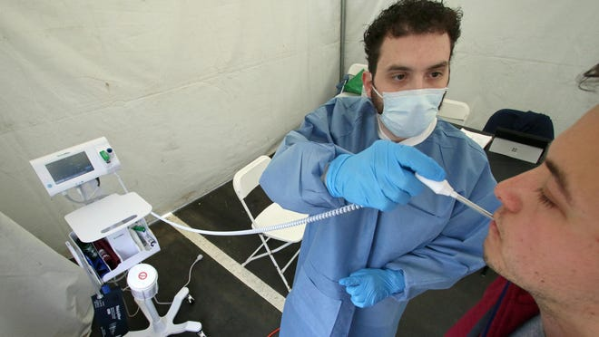 Christian Matos takes the temperature of  Gavin Stewart inside the caronavirus screening tent set up in the parking area of the afc Urgent Care Family Care building on East Franklin Boulevard Thursday morning, March 26, 2020.