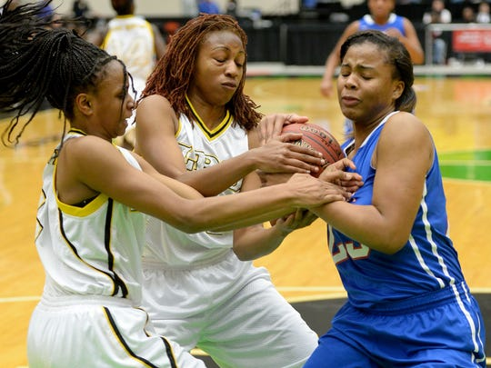 Pine Forest's Britney Snowden, right, grabs a rebound from Winter Haven's Diamond Battles and Maddison Wells during the Class 6A semifinal in the FHSAA Girls Basketball Finals at The Lakeland Center on Friday. Pine Forest defeated Winter Haven, 50-44.