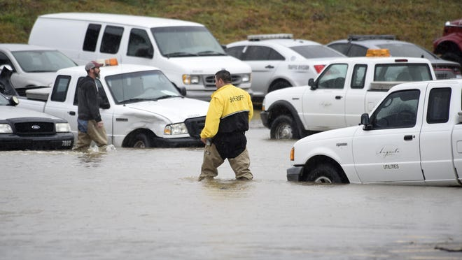 Men wear hip waders as they walk around the flooded parking lot at the City of Augusta's fleet maintenance facility Dec. 13. Replacing aging or damaged city fleet, mainly public safety vehicles, highlighted a Tuesday Augusta Commission discussion about the Sales Tax 8 package.