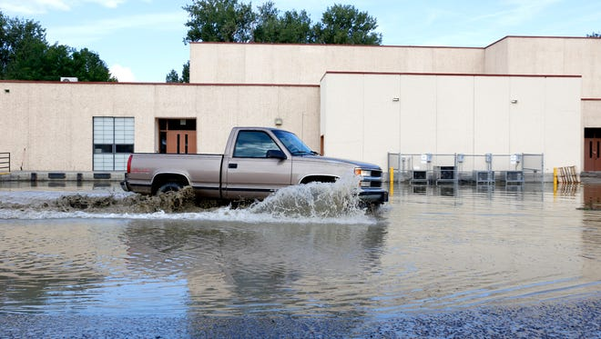 A vehicle drives through a heavily flooded parking lot on the back side of the school, Thursday, Aug. 27, 2015, at Aztec High School in Aztec, N.M.