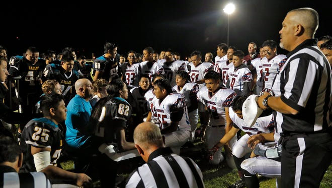 Navajo Preparatory School and Shiprock High School football players meet on the field with team coaches and referees to pray for Navajo Preparatory School's Jonathan Slim after he was injured in a play, Friday, Sept. 25, 2015, at Eagle Stadium in Farmington.