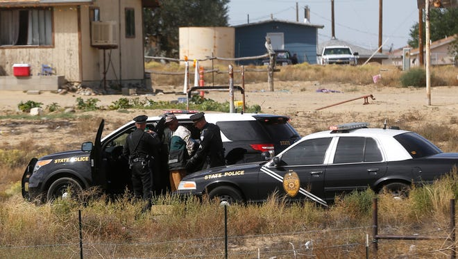 Members of local law enforcement agencies apprehend a suspect Friday along Navajo Route 36 in Lower Fruitland.