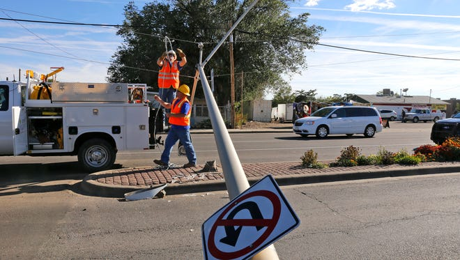 Farmington Electric Utility employees work on a downed light pole Friday near the intersection of East Main Street and Schofield Lane in Farmington.