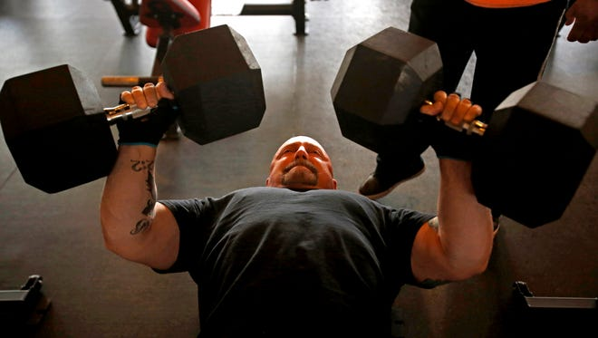 Lead trainer Terry Pearson, lifts free weights on Thursday, Oct. 29, 2015 at Fitness World in Farmington. cq