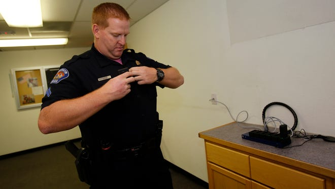 Cpl. Jared Stock, day shift supervisor for the Farmington Police Department, puts on his body camera Friday at police headquarters.