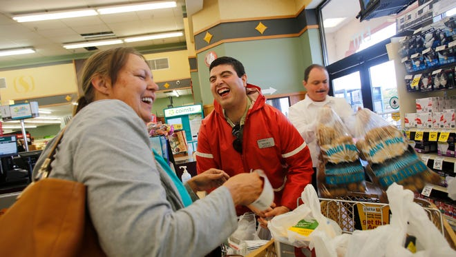 Taylor Kempton laughs with a customer, Tuesday at Safeway on West Main Street in Farmington.