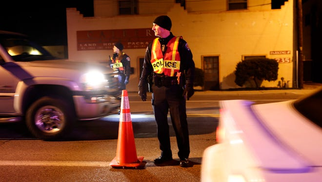 Farmington police Lt. Taft Tracy directs traffic at a sobriety checkpoint on East Main Street in Farmington last December.