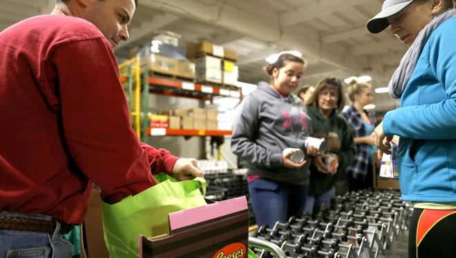 Peter Marabella fills bags with food for needy families on Dec. 13, 2014, at ECHO Food Bank in Farmington.