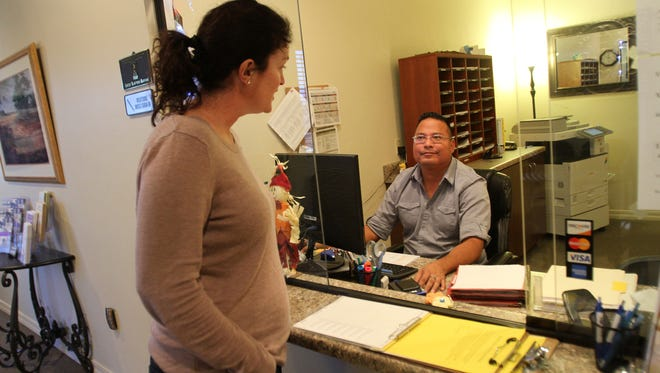 Therapist Amy Hackmeier talks with a co-worker, receptionist Chris Tsosie, on Tuesday at Desert View Family Counseling in Farmington.