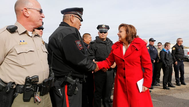 Gov. Susana Martinez shakes hands with law enforcement officials on Dec. 10 before a press conference about drunken driving penalties off U.S. Highway 64 between Farmington and Bloomfield.