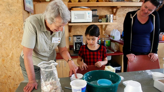Riverside Nature Center volunteer Susan Carlson, left, works with Emma Murillo as the girl's mother, Nicole Murillo, looks on as they make fossils out of plaster during Earth Science Day on Feb. 7 at the Riverside Nature Center in Farmington.