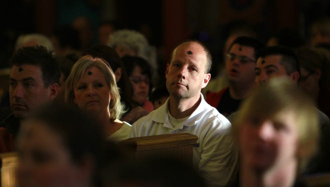 Sacred Heart Catholic Church parishioners wear ashes on their foreheads during Ash Wednesday services on March 5, 2014, at the church in Farmington.