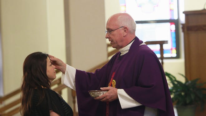 A churchgoer receives ashes from Father Tim Farrell during an Ash Wednesday service on March 5, 2014, at Sacred Heart Catholic Church in Farmington.