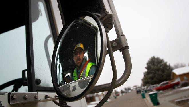 Armando Ortiz, a driver with Waste Management, picks up trash bins on Wednesday along Wellington Street in Farmington. Ortiz was among the Waste Management garbage truck drivers who received training earlier this month on how to help local law enforcement by reporting suspicious activities.