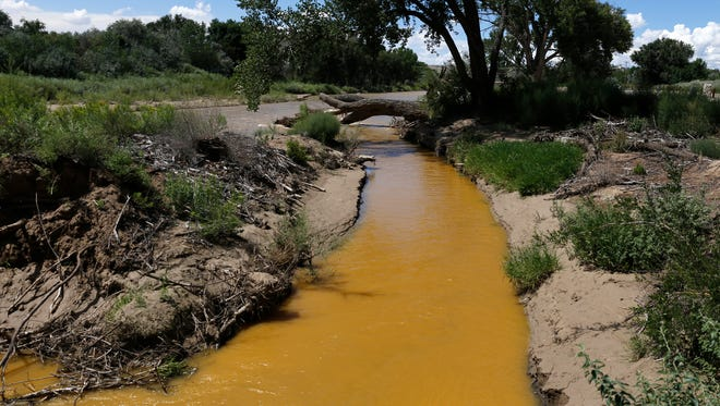Discolored water from the Gold King Mine spill is seen draining from the Animas River into the San Juan River on Aug. 8 at the rivers' confluence at Among the Waters Park in Farmington.