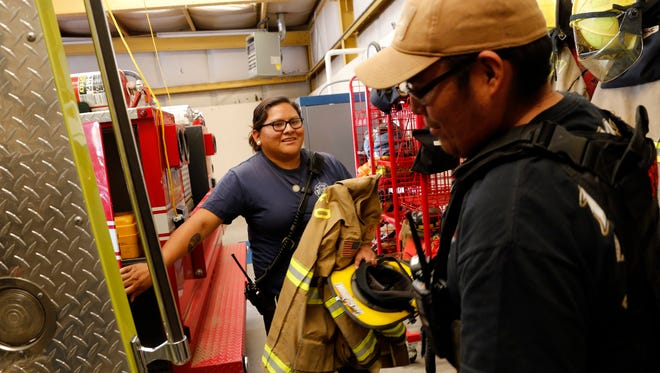 Firefighters Leigh Ann Nez, left, and Derrick Woody collect their gear Oct. 22 as they prepare to respond to an emergency at San Juan County District 12 Fire Station in Shiprock.