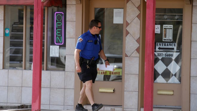 Farmington Police Officer Greg Ericksen checks on Thursday to see whether a business in downtown Farmington was damaged overnight.