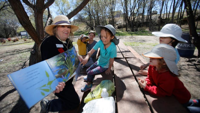 Riverside Nature Center Education Specialist Donna Thatcher reads to children on Tuesday during a picnic at Animas Park in Farmington. The center is planning an Earth Day celebration Saturday.