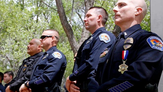 Farmington police officers listen to the keynote speaker during last year's San Juan County Law Enforcement Memorial on May 15 at All Veterans Memorial Plaza at Berg Park in Farmington.