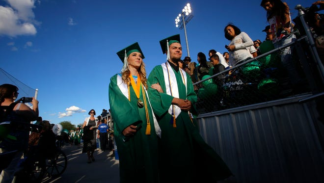 Emily Bliss and Kyle Gonzales enter Ricketts Park May 19 for their high school graduation ceremony in Farmington. The city had the seventh-lowest graduation rate in the country for 2013, according to a new study.