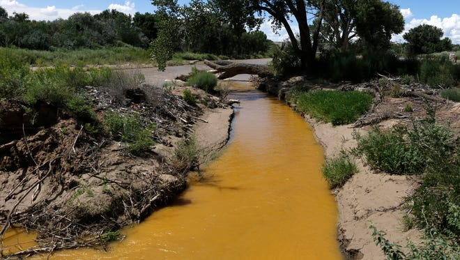 Discolored water is pictured in the Animas River near its confluence with the San Juan River in Farmington on Aug. 8, a few days after the Gold King Mine spill.