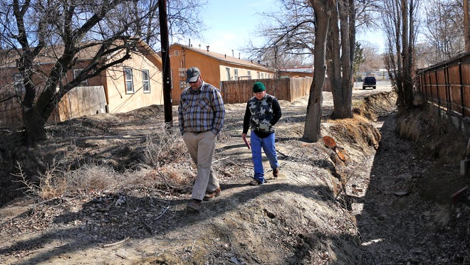 Jim DeAngelo, left, a mitigation project leader with AECOM, and Sherrick Campbell, a water resource engineer with AECOM, walk along the Blanco Arroyo near East Blanco Street in Aztec on Feb. 25.