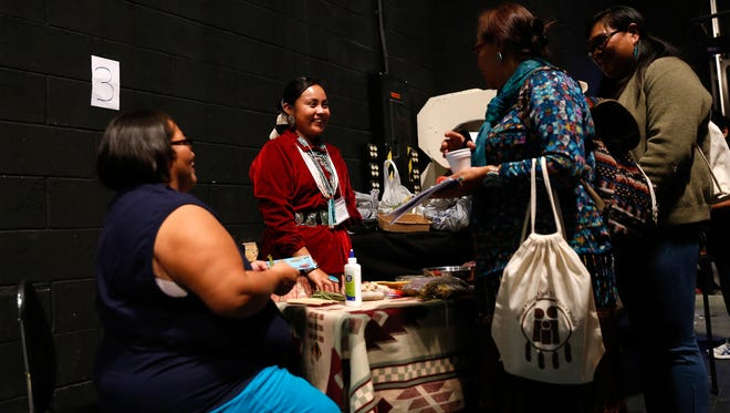 Traditional herbalist Lynelle Washburn, second from the left, talks with workshop participants on Friday during the Celebration of Women Conference at the Phil L. Thomas Performing Arts Center in Shiprock.