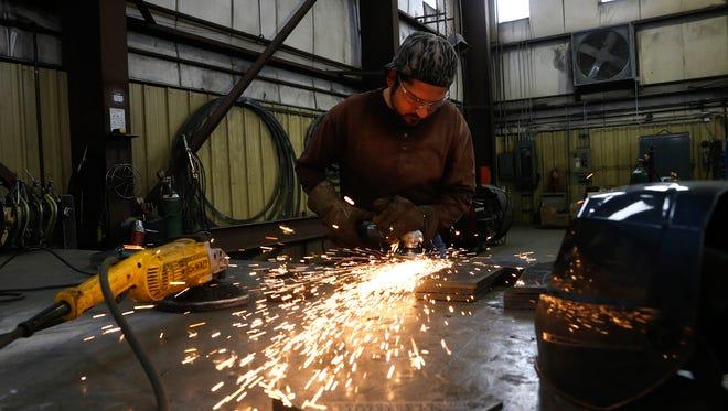 Rodrigo Baez, a welder with Mining Equipment Inc., works on Nov. 3 at the fabrication shop in Farmington.