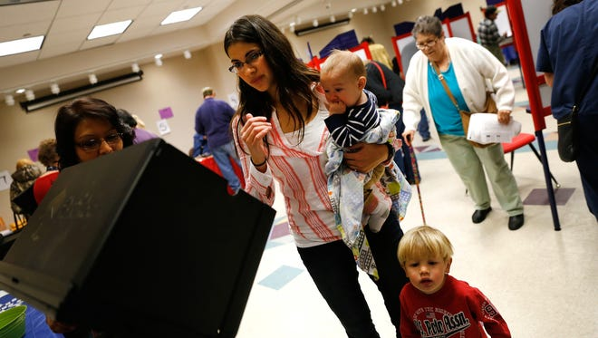 Tasha Blomstedt casts her ballot with her children, Jacob Blomstedt, on her hip, and Nathan Blomstedt Frida at the Farmington Museum at Gateway Park.