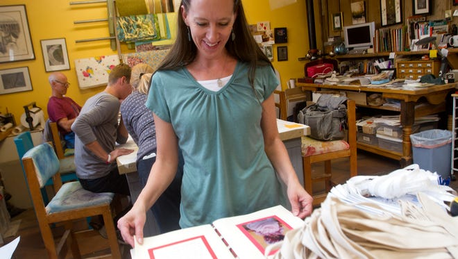 """Tara Churchill looks over a book called """"The Secret Life of Toys"""" on Nov. 16 at Artifacts Gallery in Farmington. Bev Taylor, the owner of Artifacts Gallery, compiled the book after the gallery hosted a Christmas-themed show in 2005 that focused on toys."""