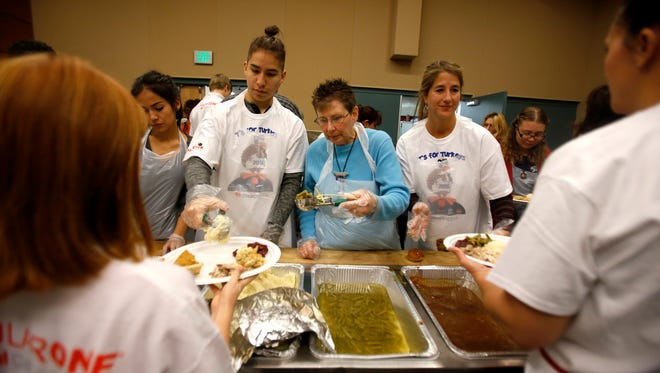 From left, Ethan Hansen, Kris Head and Patty Hooper serve food on Nov. 26 during last year's Thanksgiving dinner at the Farmington Civic Center.