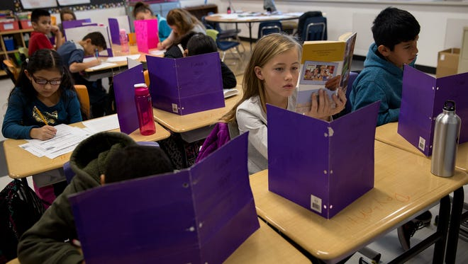 At center, fourth grader Peyton Reynolds reads her book in class on Tuesday at  Northeast Elementary School in Farmington.