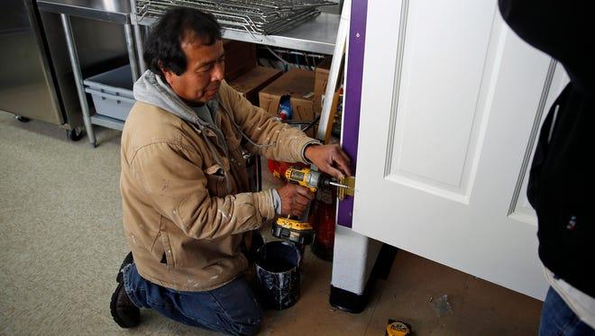 Phil Thomas installs a door on Thursday, Jan. 26, 2017, at the new Munchies sandwich shop in Farmington.
