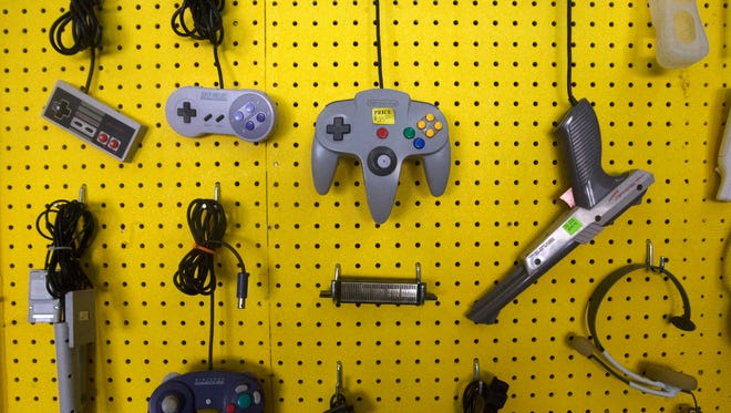 In this Friday, Feb. 17, 2017 photo, gaming controllers are displayed at Oldskool Gaming in Farmington, N.M. The new store and game room that recently opened its doors in downtown Farmington is targeting fans of vintage video game systems.