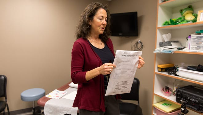 Sexual Assault Services of New Mexico Executive Director Eleana Butler displays a rape kit test Monday at her organization's offices in Farmington.