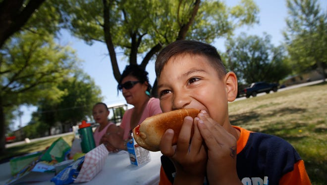 Abel Archuleta enjoys lunch with his grandmother Joann Atencio and sister Nevaeh Archuleta May 31 in Bloomfield during the inaugural Summer Food Kick Off event.