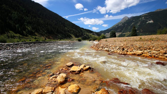 The confluence of Cement Creek, at right, merges with the Animas River, left, Monday, Aug. 10, 2015, in Silverton, Colo.