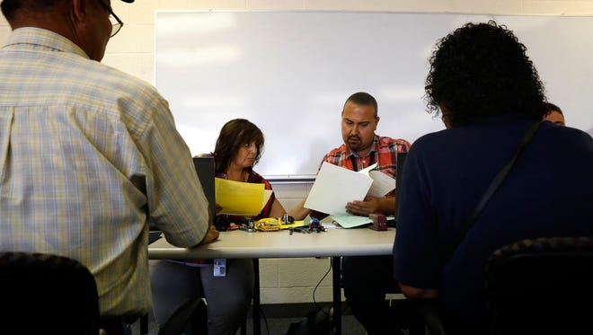State of New Mexico registrar Renee Valencia and state of New Mexico quality assurance coordinator George Dominguez look over paperwork for birth certificates for Thomas Dobey, left, and Bessie Paul, right, on Sept. 22 at the Northern Navajo Agency Nataani Nez Complex in Shiprock.